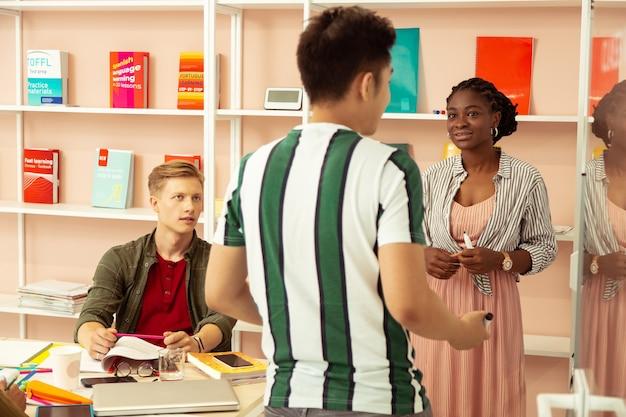 Gut vorbereitet. erfreute afroamerikanerin, die in der nähe des boards steht, während sie ihrem schüler zuhört
