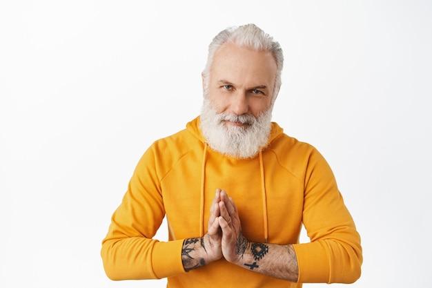 Gutaussehender älterer mann, der um hilfe bettelt, etwas braucht, namaste zeigen, beten, betteln geste. alter mann mit tattoos bedankt sich und verbeugt sich höflich, weiße wand