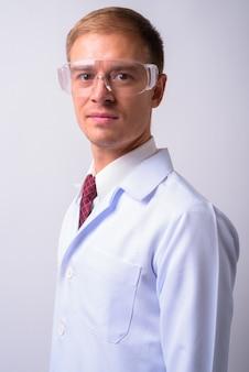 Gutaussehender arzt als wissenschaftler, der eine schutzbrille gegen leerraum trägt