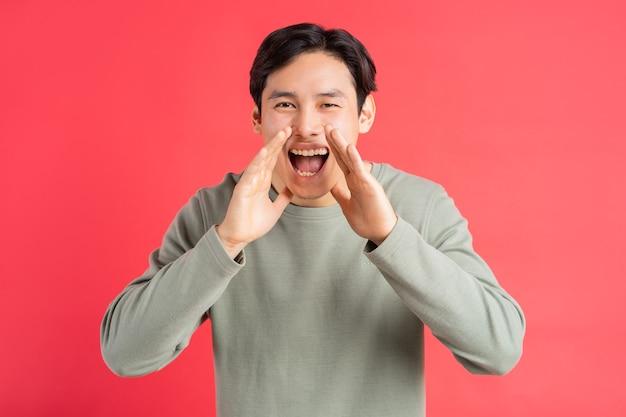 Gutaussehender asiatischer mann, der seinen mund mit seinen händen bedeckte, schrie vor freude