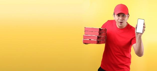 Gutaussehender asiatischer mann in der roten kappe, die italienische pizza der lebensmittelbestellung in pappkartons lokalisiert hält, die handy mit leerem weißem leerem bildschirm hält.
