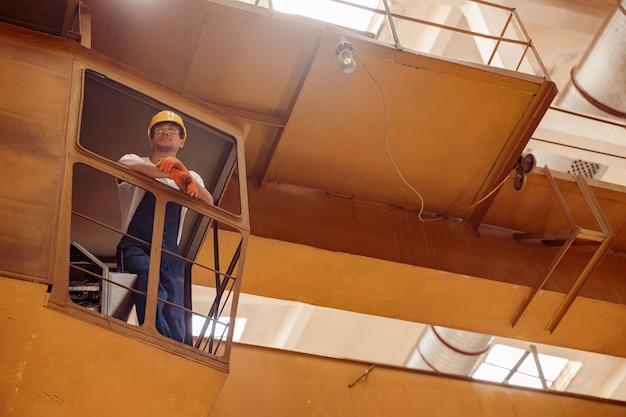 Gutaussehender bauarbeiter, der in der fahrerkabine des laufkrans sitzt