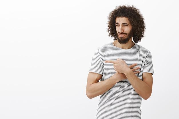 Gutaussehender erwachsener bärtiger mann mit afro-frisur, der mit verachtung und zweifel nach rechts zeigt und aussieht und den kerl verspottet, ohne an seinen sieg zu glauben