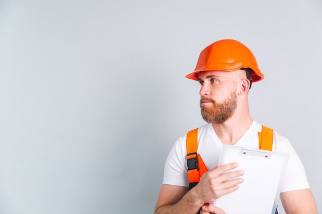 Gutaussehender ingenieur beim bau von schutzhelmen an grauer wand hält weiße zwischenablage