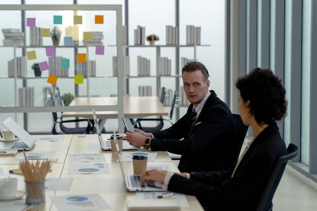 Gutaussehender kaukasischer geschäftsmann, der beratungspartner spricht und mit freundlichkeit am besprechungstisch mit tablet-computer auf dem besprechungstisch im modernen büro diskutiert. chef und angestellter. zusammen arbeiten.