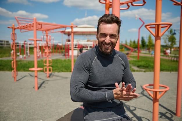 Gutaussehender kaukasischer mann, macho, sportler, athlet, lächelnd mit zahnigem lächeln, blick in die kamera auf dem sportplatzhintergrund. glücklicher attraktiver kerl, der den rest nach dem training genießt