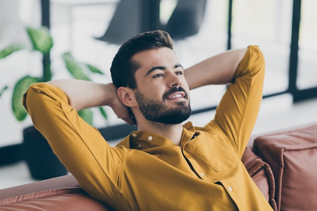 Gutaussehender kerl in hochstimmung händchenhalten hinter dem kopf sitzende bürocouch kleine kaffeepause im modernen arbeitsbereich drinnen