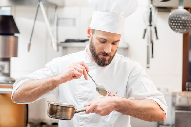 Gutaussehender koch kocht in einheitlicher verkostung von sauerkraut in der küche