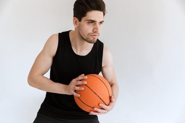 Gutaussehender konzentrierter ernster starker junger sportmann-basketballspieler, der ball isoliert hält.