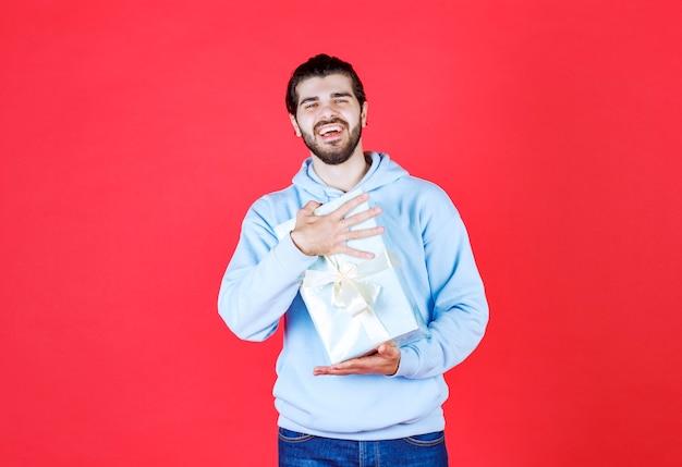 Gutaussehender mann, der eine verpackte geschenkbox mit beiden händen an der roten wand hält