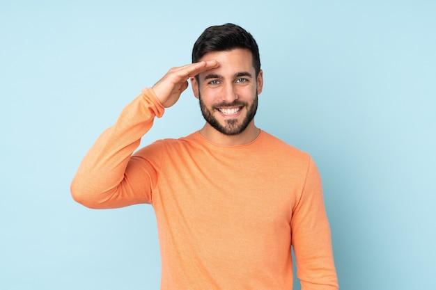 Gutaussehender mann, der mit hand mit glücklichem ausdruck über isoliertem blau salutiert