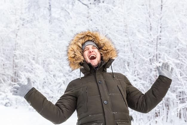 Gutaussehender mann im lustigen porträt des winterhutes auf verschneiter natur