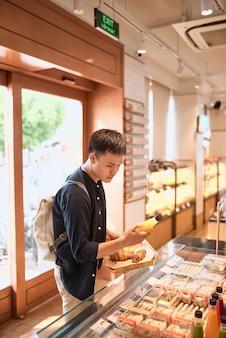 Gutaussehender mann in der örtlichen bäckerei, der ein tablett mit brötchen oder kuchen hält, der einen dessertkonsumenten kauft