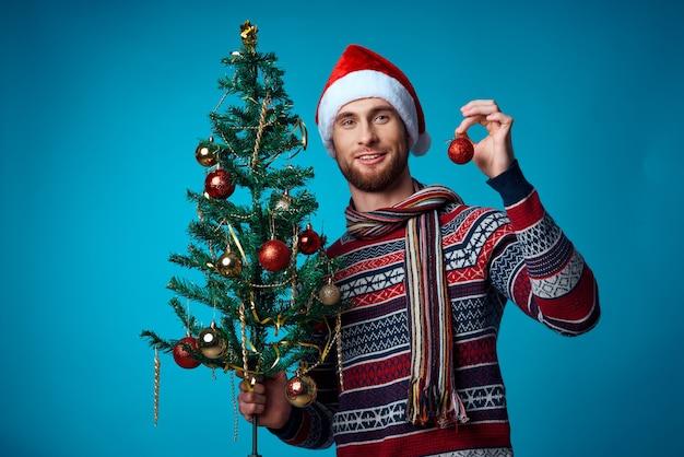 Gutaussehender mann in einer weihnachtsmütze, der ein banner-feiertagsstudio posiert
