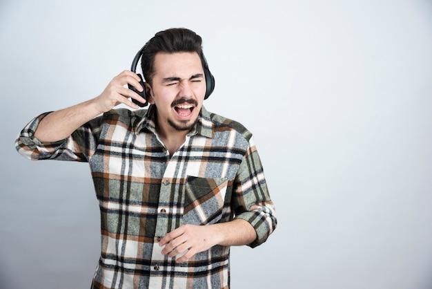 Gutaussehender mann in kopfhörern stehend und lied hörend.