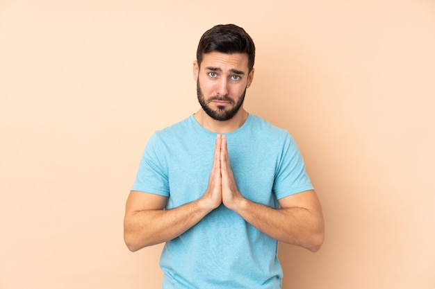 Gutaussehender mann isoliert auf beige hält handfläche zusammen