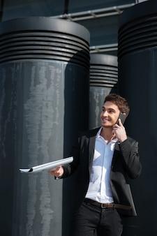 Gutaussehender mann mit dokumenten, die auf der straße am telefon sprechen