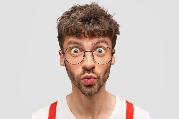 Gutaussehender überraschter mann mit fassungslosem gesichtsausdruck, runden die lippen und öffnet die augen weit, kann nicht an die neuesten plötzlichen nachrichten glauben