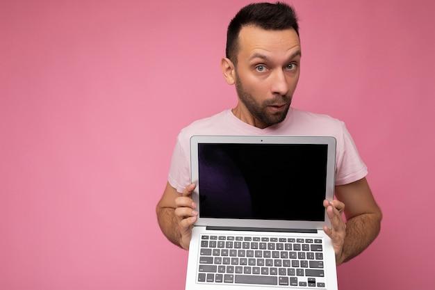Gutaussehender überraschter und erstaunter mann, der einen laptop-computer hält und die kamera im t-shirt auf isoliert anschaut