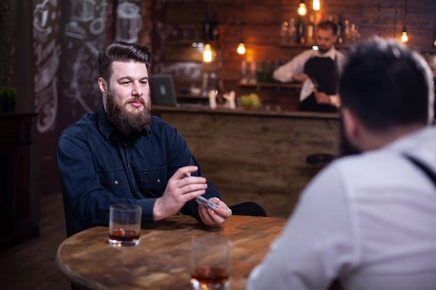 Gute alte freunde hängen bei einem glas whisky und kartenspiel ab. stilvolle männer. hübsche bärtige männer.