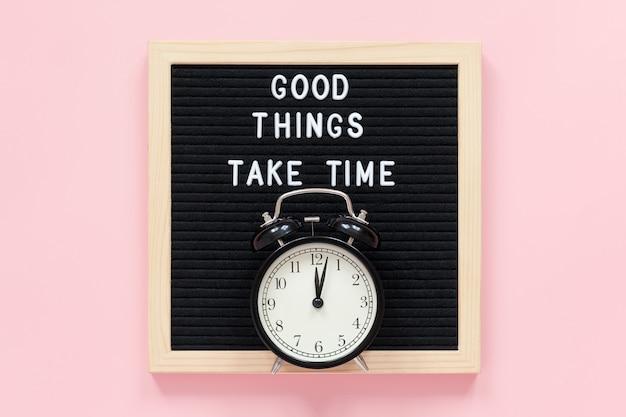 Gute dinge brauchen zeit. motivationszitat auf schwarzem briefbrett, schwarzer wecker auf rosa hintergrund. inspirierendes zitat des konzepts