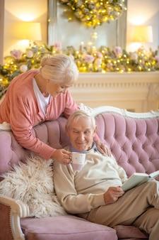 Gute ehefrau. älterer mann sitzt auf einem sofa mit einem buch und seine frau gibt ihm eine tasse tee