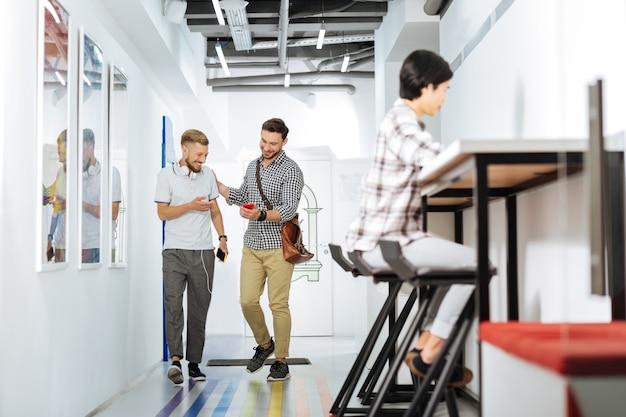 Gute freunde. fröhliche junge männer, die in einem modernen coworking space gehen und lächeln, während sie den bildschirm eines modernen smartphones betrachten