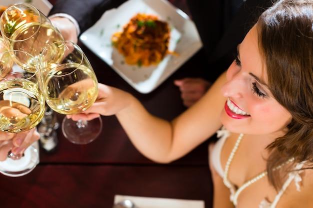 Gute freunde zum mittag- oder abendessen in einem guten restaurant, die mit gläsern anstoßen
