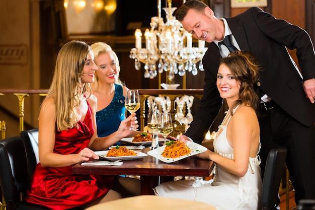 Gute freunde zum mittagessen in einem guten restaurant, kellner serviert das abendessen