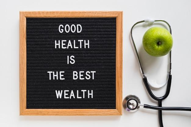 Gute gesundheit anschlagbrett mit grünem apfel und stethoskop auf weißem hintergrund