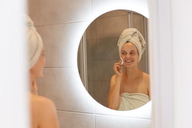 Gute junge erwachsene frau, die in ein weißes handtuch gehüllt ist, das im badezimmer vor dem spiegel posiert, reinigt das gesicht mit einem wattepad, sieht glücklich aus und lächelt, hautpflege, morgenroutine.