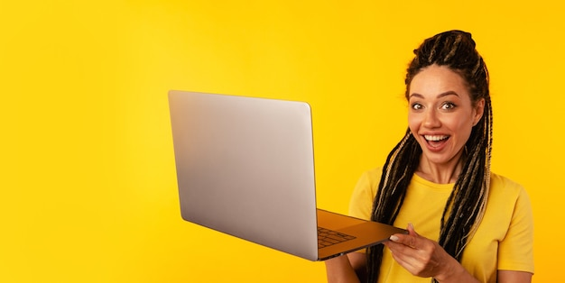 Gute laptoparbeit. frau, die kühles zeichen hält computer im gelben raum hält.