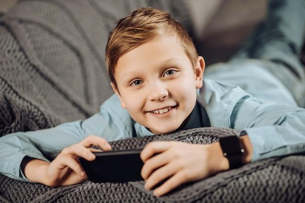 Gute laune. die nahaufnahme eines charmanten jugendlichen jungen, der auf dem sofa liegt und für die kamera posiert, während er am telefon spielt und strahlt