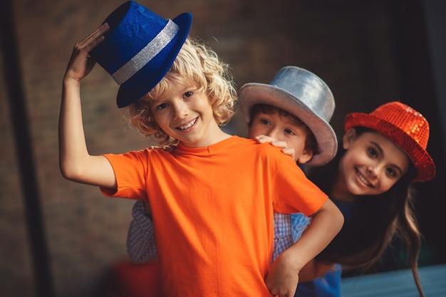 Gute laune. drei freunde in partyhüten sehen fröhlich aus