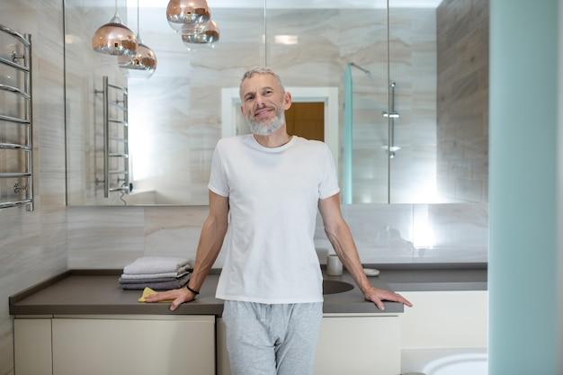 Gute laune. ein großer reifer amn steht in einem badezimmer und sieht positiv aus