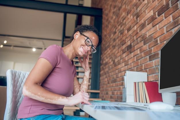 Gute laune. eine frau mit brille, die an einem computer arbeitet und glücklich aussieht