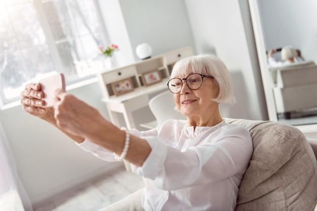 Gute laune einfangen. entzückende ältere frau, die auf dem sofa im wohnzimmer sitzt und posiert, während sie selfie nimmt
