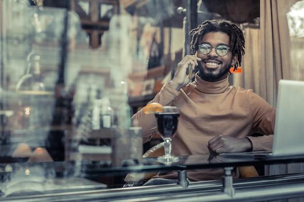 Gute laune. erfreulicher stilvoller mann, der ein lächeln auf seinem gesicht behält, während er mit partnern kommuniziert