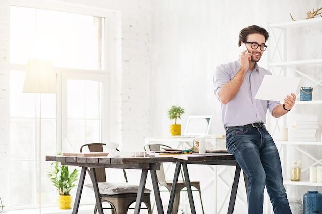 Gute laune. hübscher alarmmann, der am telefon spricht und ein blatt papier hält