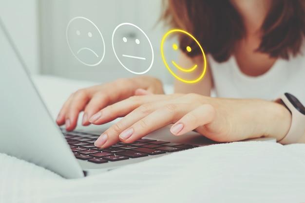 Gute-laune-konzept aus emoticon und bewertung. das mädchen schreibt mit einem laptop noten ins internet.