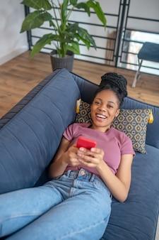 Gute laune. lächelnde schöne junge dunkelhäutige frau in freizeitkleidung mit smartphone, die zu hause auf dem sofa liegt