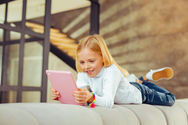 Gute laune. süße blondine hält ein lächeln auf ihrem gesicht, während sie ihr tablet benutzt