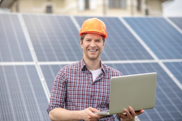 Gute momente. glücklicher junger erwachsener lächelnder mann im schutzhelm mit offenem laptop in den händen auf dem hintergrund des sonnenkollektors