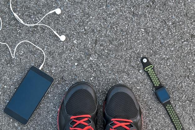 Gute musik für gute passform. abgeschnittenes foto von smartwatch, smartphone und schwarzen turnschuhen auf asphalthintergrund. mobile apps zur sportmotivation