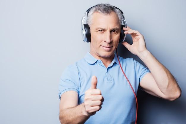 Gute musik zu hören hilft ihnen in jeder situation. porträt eines älteren mannes mit kopfhörern, der musik hört und seinen daumen nach oben zeigt, während er vor grauem hintergrund steht