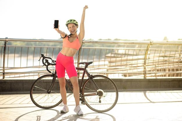 Gute nachrichten. ein mädchen mit einem fahrrad steht an der brücke mit einem smartphone in der hand