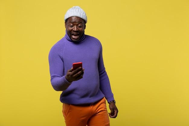 Gute nachrichten. emotionaler brünetter mann, der den mund offen hält, während er auf sein telefon schaut