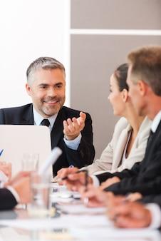 Gute nachrichten für unser unternehmen! geschäftsleute in formeller kleidung diskutieren etwas, während sie zusammen am tisch sitzen