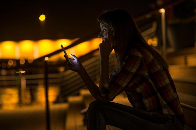 Gute nachrichten. junge glückliche frau lächelnd sms auf ihrem handy