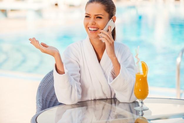 Gute nachrichten mit freunden teilen. glückliche junge frau im bademantel, die mit dem handy spricht und gestikuliert, während sie am tisch am pool sitzt